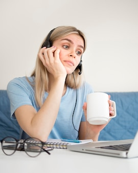 Female student drinking coffee at online course