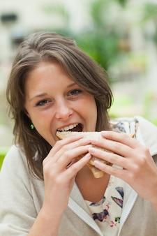 Студентка, едят бутерброд в столовой