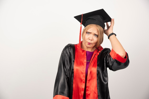 Female student in gown looking surprised on white.