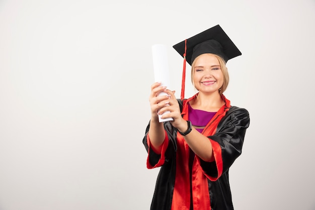 Female student in gown received diploma on white.