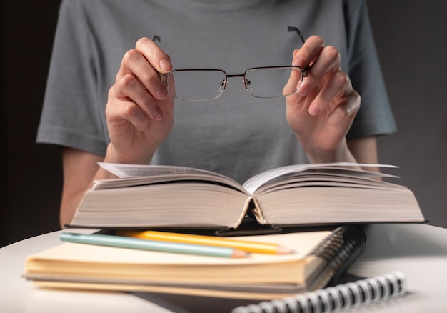 Female student hands close up, holding eyeglasses and book or textbook, searching for information and reading at night.