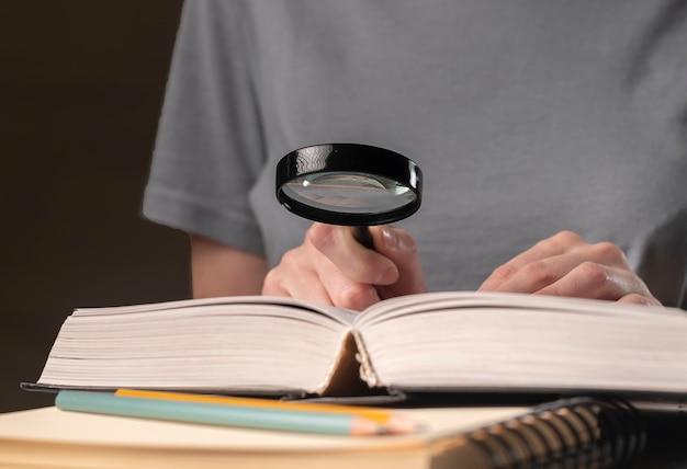女子学生の手をクローズアップし、虫眼鏡と本や教科書を持って、情報を探し、夜に読書をします。