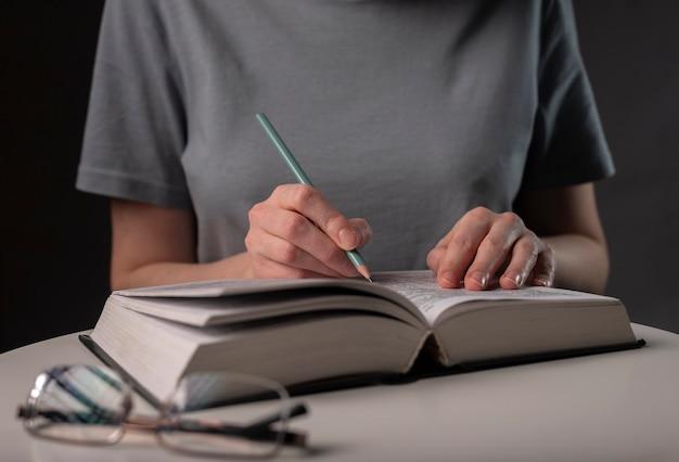 鉛筆を持って本を読んでいる女子学生の手は、夜のテーブルで試験の準備をします。教育の概念。