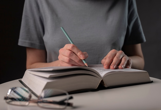 Female student hands holding pencil and reading book, prepare for exam at table at night. education concept.