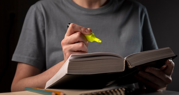 Female student hands holding yellow highlighter and reading book or textbook, making notes, underlines, prepare for exam at table at night. education concept.