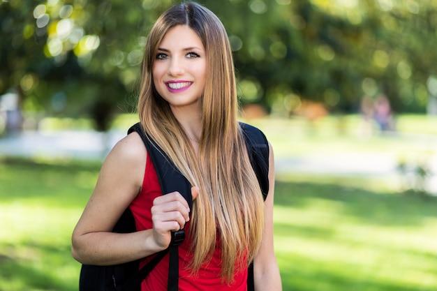 Студентка, проведение книги на открытом воздухе в парке и улыбается