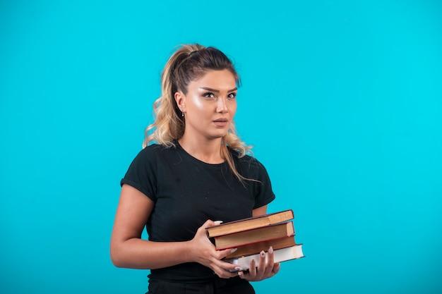 大量の本を持っている女子学生。