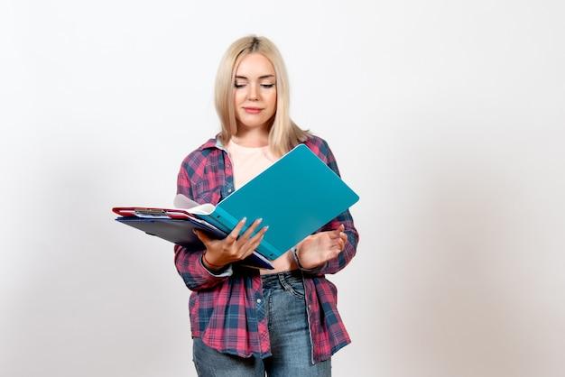 Студентка держит разные файлы и читает на белом
