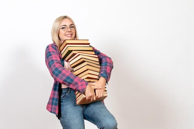 Студентка держит разные тяжелые книги и улыбается на белом