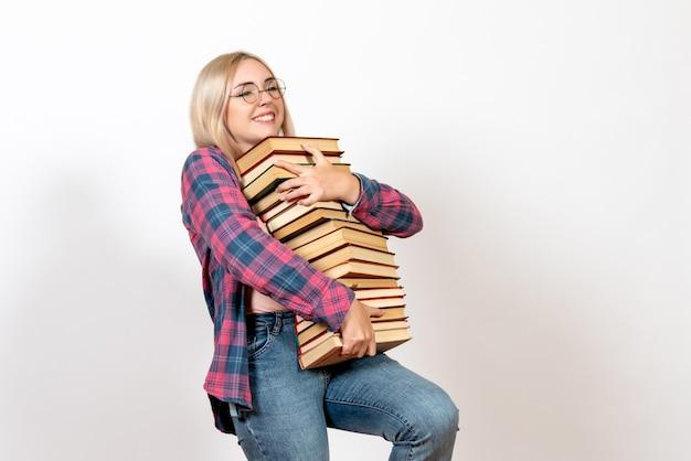 Studentessa in possesso di diversi libri pesanti su bianco chiaro