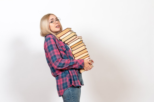 Female student holding different heavy books on white