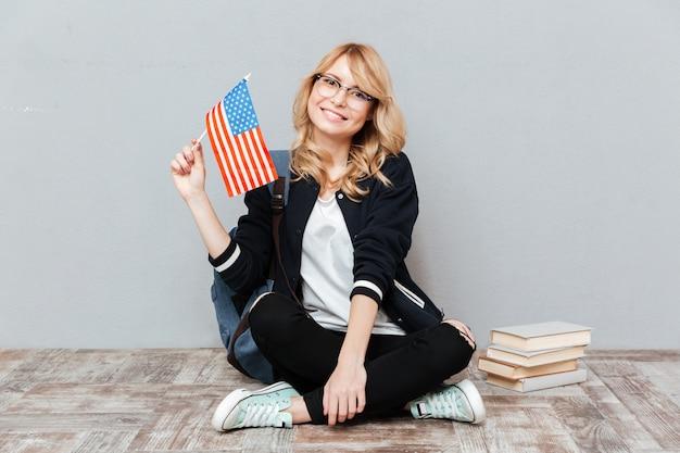 床に座ってアメリカの国旗を保持している女子学生