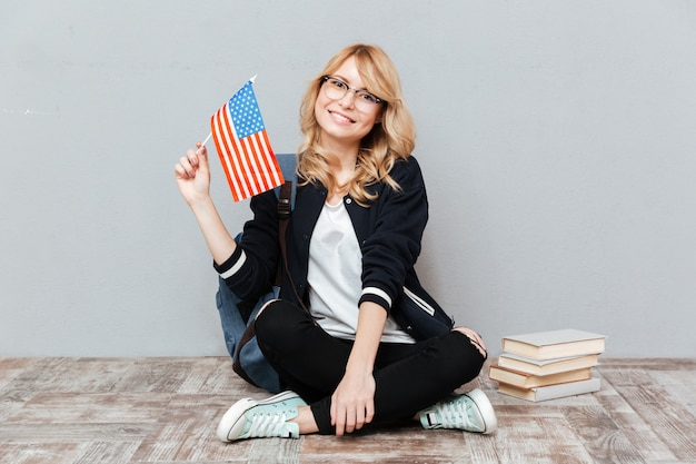 Female student holding flag of usa sitting on the floor