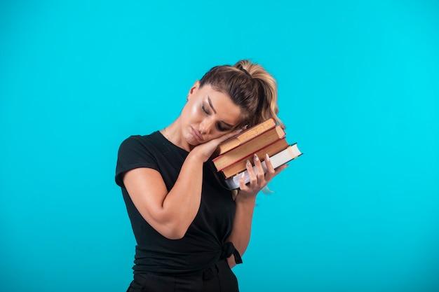 Studentessa in possesso di un pesante stock di libri e ascoltandoli.
