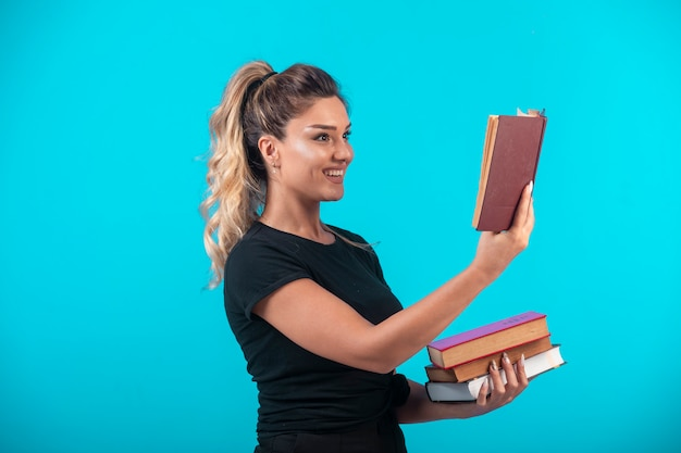 Female student holding a heavy stock of books and reading one of them.