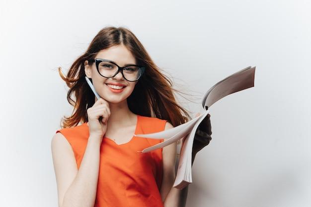 サンドレスとメガネの白い背景と鉛筆を手に女子学生