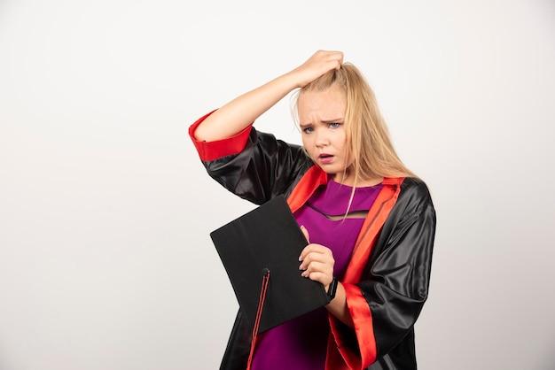 白い背景に彼女の帽子を保持しているガウンの女子学生。高品質の写真