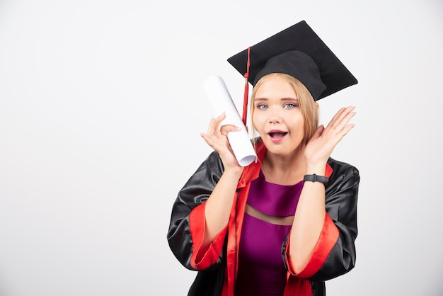 ガウンの女子学生は、白い背景の上の卒業証書を受け取りました。高品質の写真
