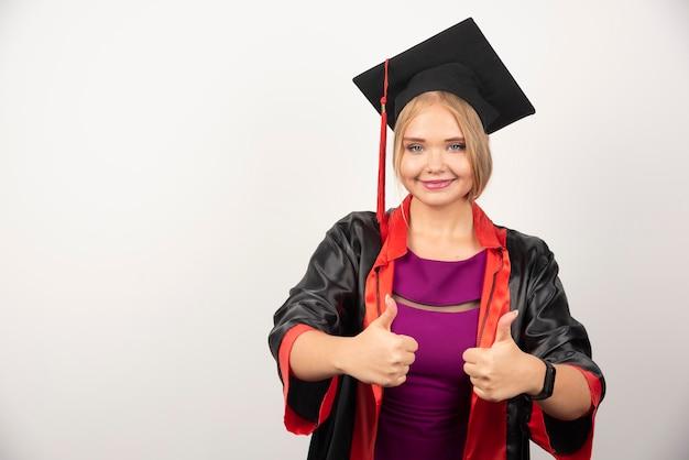 白い背景に親指を立てながら笑顔のガウンの女子学生。高品質の写真