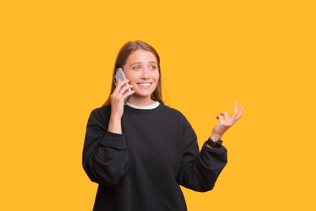 女子学生が電話で話し、身振りで示しています。