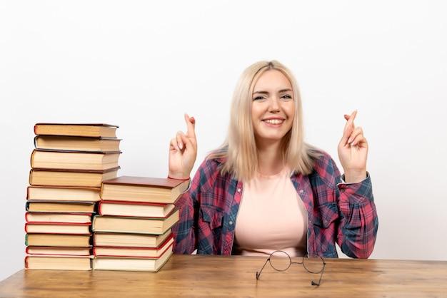 白で指を交差させて本を持って座っている女子学生