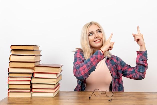 白の本と一緒に座っている女子学生
