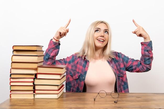 Studentessa appena seduta con i libri che puntano sul bianco