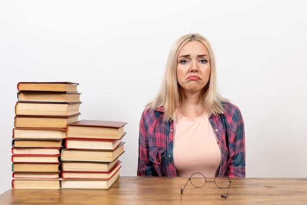 흰색에 슬픈 표정으로 책과 함께 앉아있는 여성 학생