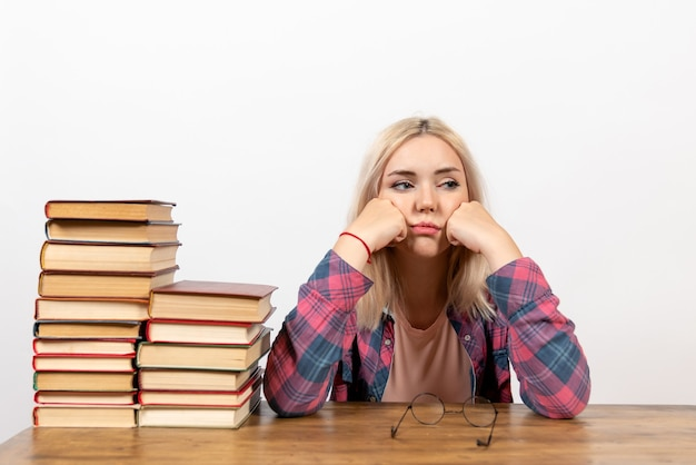 Студентка просто сидит с разными книгами на белом