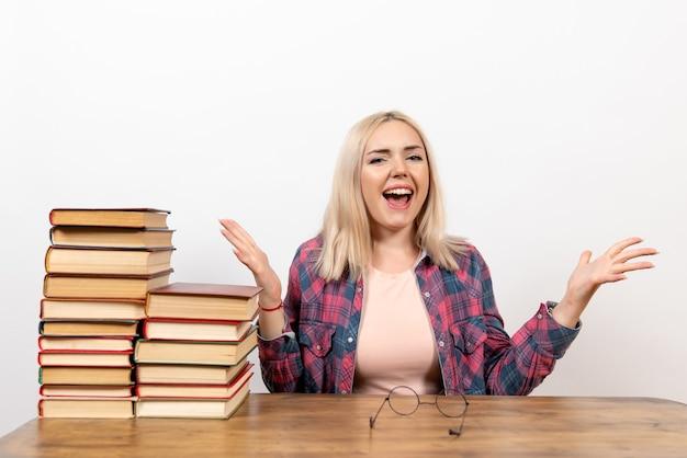Studentessa appena seduta con diversi libri sul pavimento bianco lettura ragazza biblioteca libri scolastici dello studente