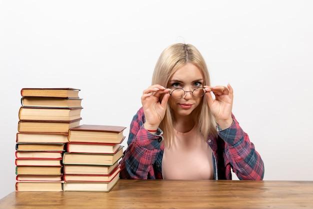Studentessa appena seduta con diversi libri su bianco