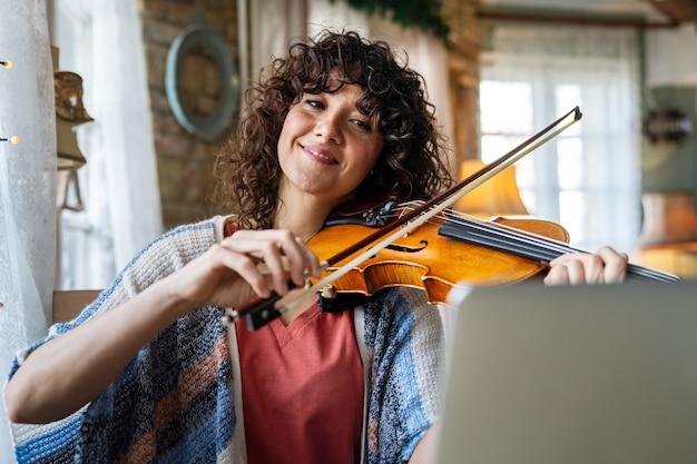 Студентка учится играть на скрипке онлайн с помощью ноутбука дома