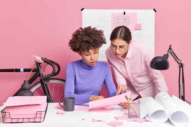 建築学部の女子学生が、重要なタスクについて、ブレインストロームの周りに青写真とステッカーを貼って、オフィスの机で紙の文書のポーズを注意深く話し合う
