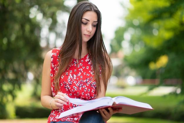 公園で本を読んでいる女子学生