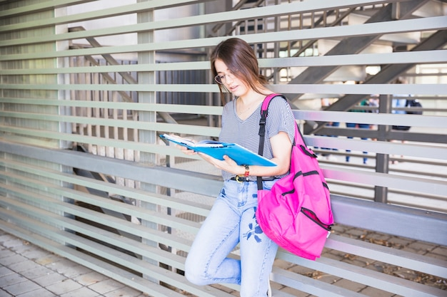 Female student reading textbook near wall