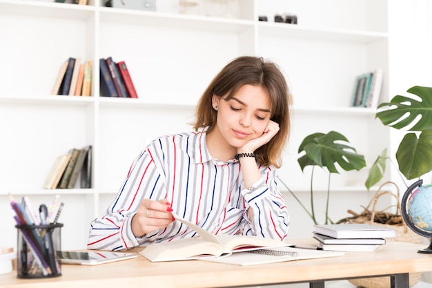 Female student reading at wooden desk