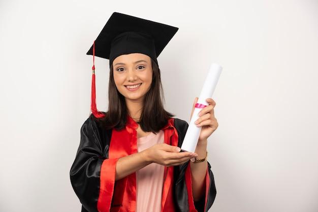 白い背景の上の卒業証書を示す女子学生。