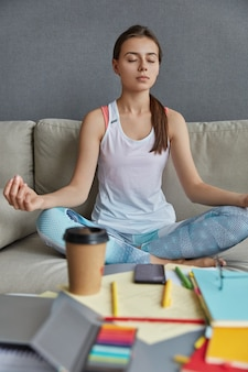 Female student sits in lotus pose, feels peace breathing, finds inspiration in meditation, drinks coffee