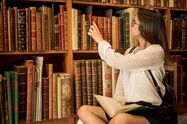 Студентка сидит со скрещенными ногами с открытой книгой в библиотеке