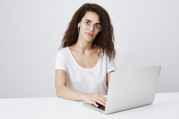 Studentessa seduta scrivania, utilizzando laptop e ascoltare musica in auricolari