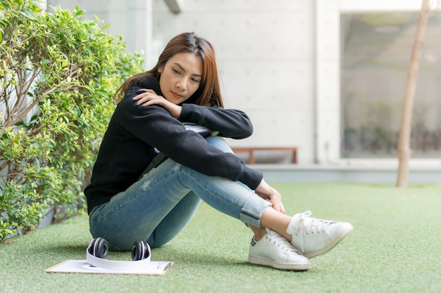 Female student sitting on lawn bench at campus