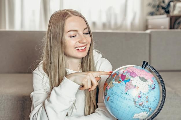 Студентка сидит на диване у себя дома и показывает пальцем на маленький глобус