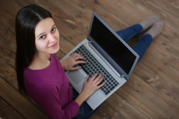 Студентка сидит на полу с ноутбуком и учиться