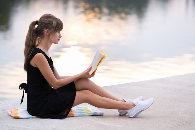 Female student sitting in summer park reading textbook outdoors. education and sudy concept.