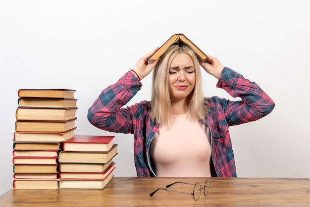 책과 함께 앉아서 화이트에 읽는 여자 학생
