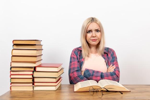 本と一緒に座って、白でポーズを読んで読む女子学生
