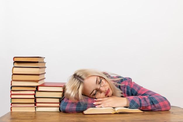 本を持って座っている女子学生が疲れを感じ、白で寝ている 無料写真