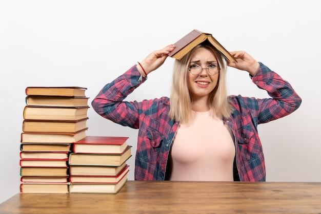 Studentessa seduta con libri in possesso di uno sulla sua testa su bianco