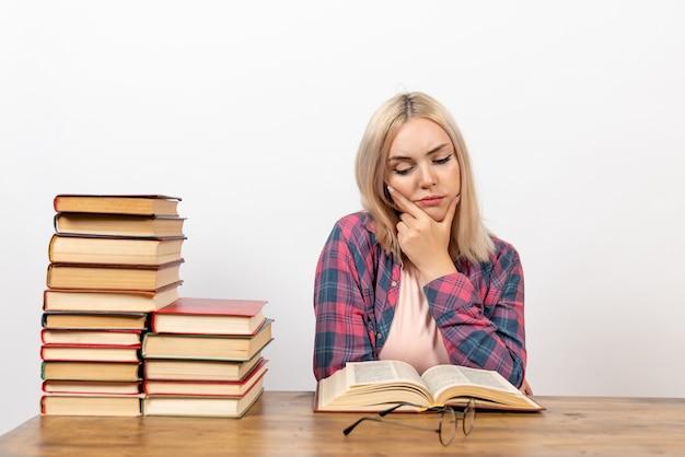 白で読書と思考の本と一緒に座っている女子学生