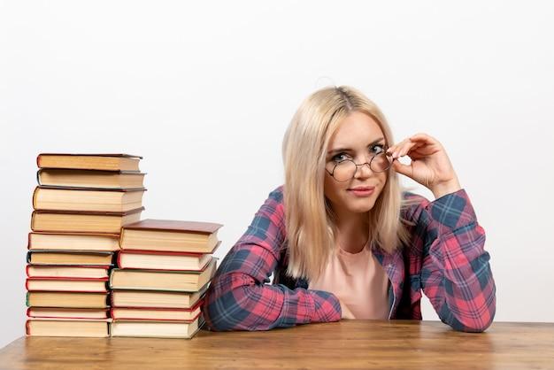 明るい白の別の本と一緒に座っている女子学生
